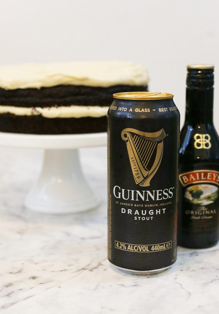 Close up of Guinness Beer and Baileys bottle in front of a cake