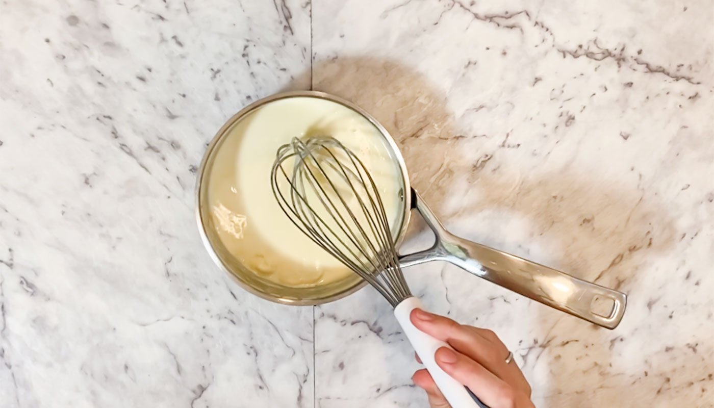 Melting white chocolate and cream together in a saucepan